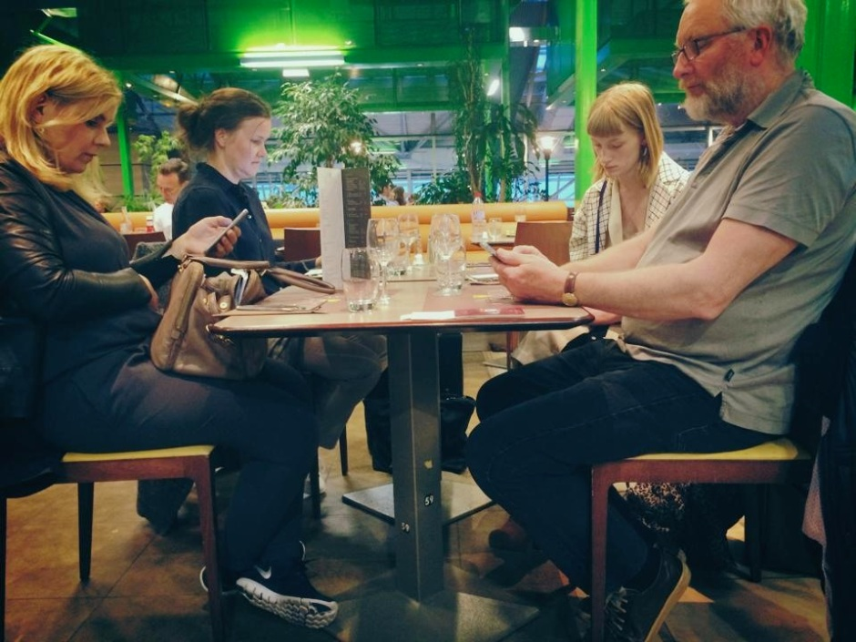 Antisocial media: Four friends at a restaurant in Nice Airport, France
